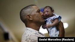 Бразилиялық Зика вирусымен байланысты микроцефалия дерті анықталған ұлын ұстап тұр. Ресифе, Бразилия, 26 қаңтар 2016 жыл.