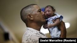 Бразилец держит сына, у которого диагностирована микроцефалия, развитие которой связывают с вирусом Зика, Ресифе, январь 2016 года.