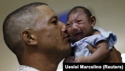Отец в госпитале бразильского города Ресифе держит на руках своего сына, родившегося с микроцефалией. 26 января 2016 года
