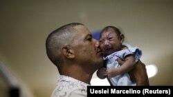 Бразилец держит на руках сына, родившегося из-за перенесенной его матерью лихорадки Зика с микроцефалией. Ресифи, 26 января 2016 года.