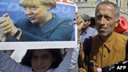 Djevojčica drži sliku Angele Merkel na maršu izbjeglica u Budimpešti, 4. septembar 2015.