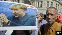 -- A migrant girl holds a poster of German Chancellor Angela Merkel as migrants walk in Budapest downtown after leaving the transit zone of the main train station, September 4, 2015