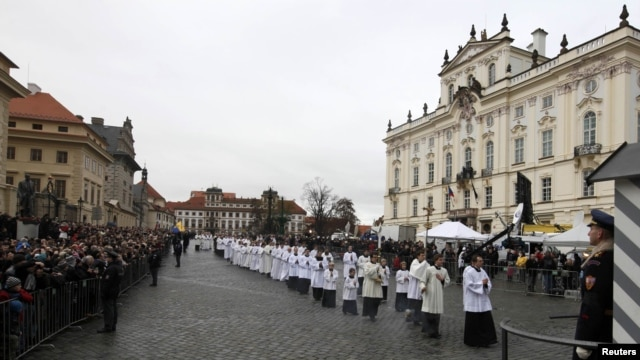 Catholic priests walk in line to attend the funeral ceremony at St. Vitus Cathedral.