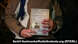 Обложка книги в руках у девушки, пришедшей к зданию суда во время оглашения решения