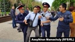 Полицейские задерживают человека, находившегося на месте, которое запрещенное в стране движение обозначило как площадку для проведения митинга. Алматы, 10 мая 2018 года.