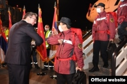 Serbian President Aleksandar Vucic (without mask) welcomes Chinese health experts and a planeload of Chinese medical supplies to Belgrade on March 21, 2020.