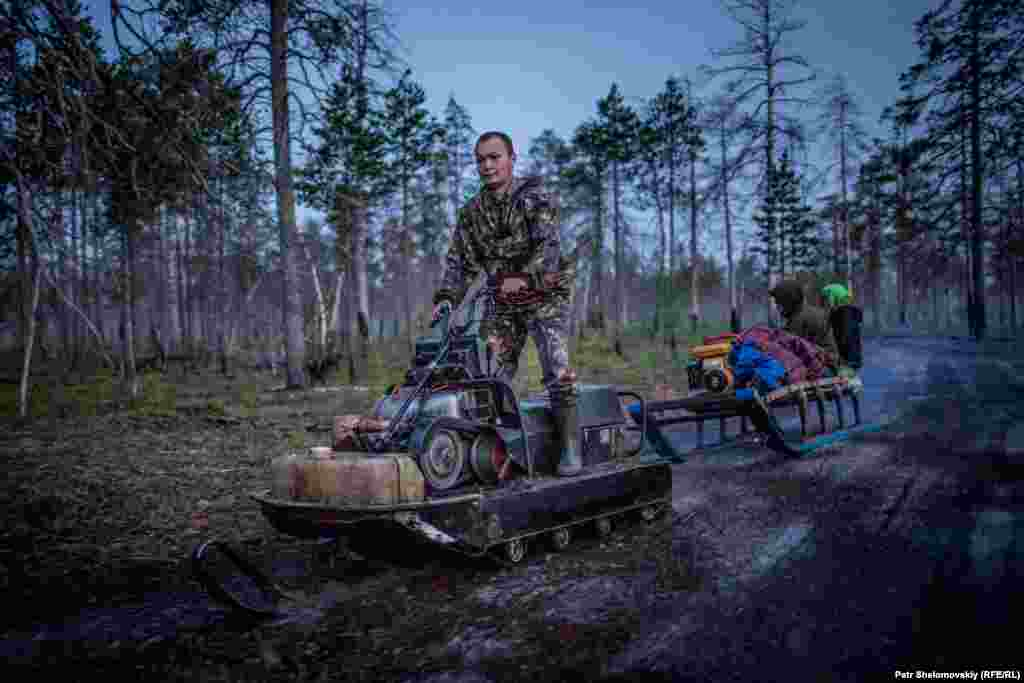 Dmitry Laziamov rides a snowmobile through the woods.