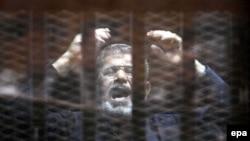 Мохаммед Мурси в клетке в суде незадолго до смерти