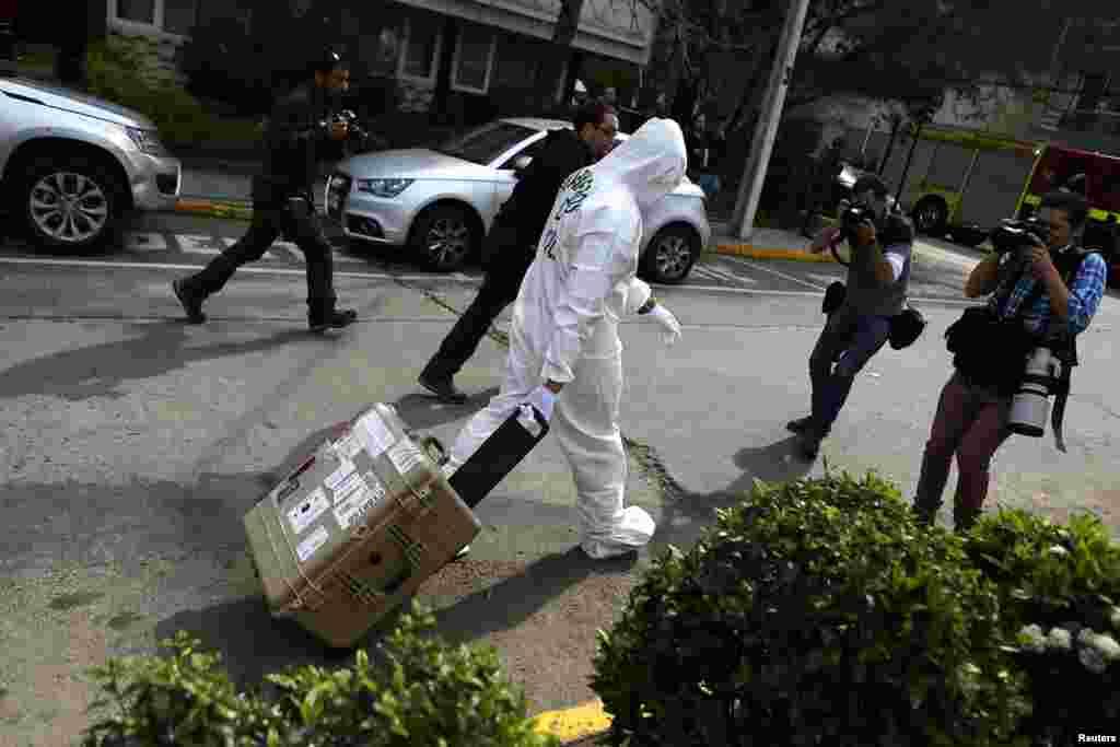 """Чили үкіметі ел астанасы Сантьяго қаласының метросы маңында 8 қыркүйек күні түс уақытында болған жарылысты """"террористер ұйымдастырды"""" деп мәлімдеді. Жарылыс салдарынан 14 адам жараланған. Суретте: Жарылыс болған жерде жүрген полиция мен журналистер. Сантьяго, 8 қыркүйек, 2014 жыл."""
