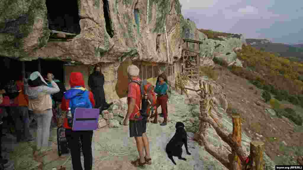 К подножию скалы, в которой находится монастырь, ведет крутая каменистая тропа. Она проходит в зарослях кизильника, колючего держи-дерева, можжевельника колючего. Тропа усеяна глиняными черепками – остатками амфор
