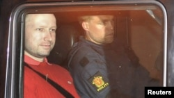 Suspect Anders Behring Breivik (left), accused of a killing spree and bomb attack in Norway, sits in the rear of a vehicle as he is transported from a courthouse in Oslo on July 25.