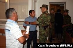 Конвой уводит старшего лейтенанта Галыма Оразгалиева из зала суда. Алматы, 19 августа 2014 года.