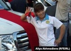 Лондон олимпиадасының чемпионы, ауыр атлет Майя Манеза сыйға алған Toyota Land Cruiser-200 көлігінің қасында тұр. Талдықорған, 15 тамыз 2012 жыл.