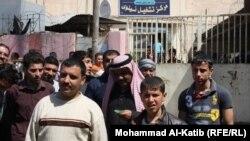 مراجعون يخرجون من مركز للتشغيل في الموصل