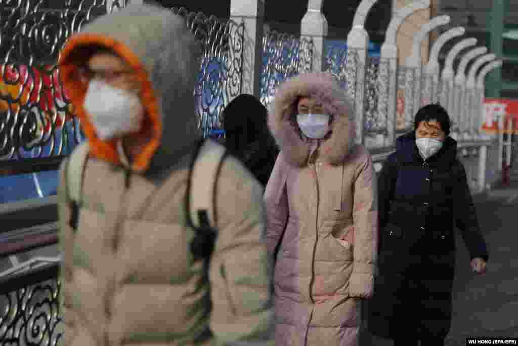Пассажиры в масках на железнодорожном вокзале в Пекине, 24 января 2020 года