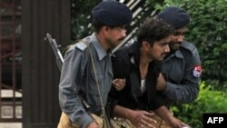 Pakistani police officers help an injured colleague after a suicide attack in Islamabad