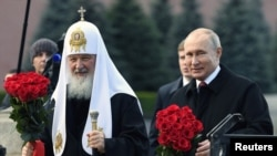 Russian President Vladimir Putin and Patriarch Kirill lay flowers at the monument on the Red Square near the Kremlin, marking National Unity Day in Moscow on November 4, 2018.