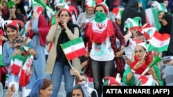 Iranian women cheer ahead of the World Cup Qatar 2022 Group C qualification football match between Iran and Cambodia at the Azadi stadium in the capital Tehran on October 10, 2019.
