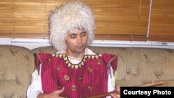 Murad Rakhimov, dressed in traditional Turkmen attire, playing the dutar