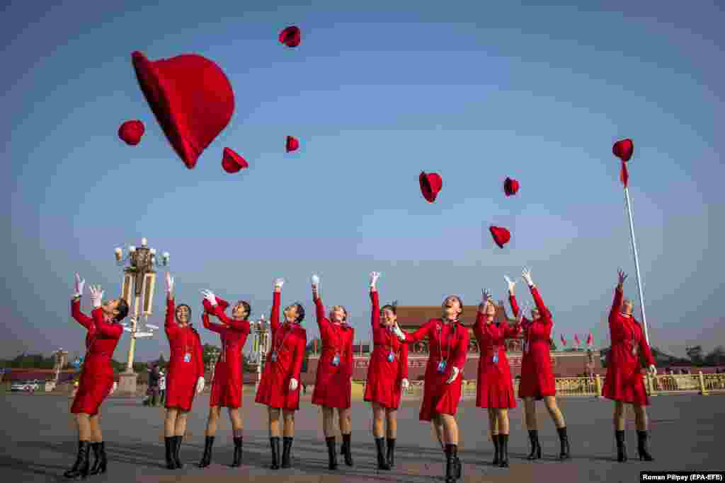 Hostesses jump in the air and throw their hats on Tiananmen Square during the closing session of the 19th Communist Party Congress in Beijing on October 24. (epa-EFE/Roman Pilpey)