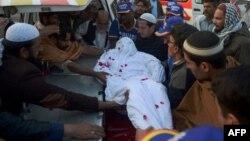 Пәкістандағы жарылыстардың бірінде қаза тапқан адамның мәйітін алып кету сәті. Карачи. 3 ақпан 2015 жыл