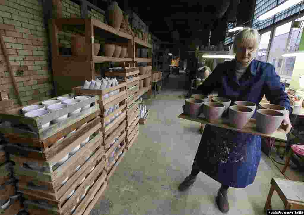A worker carries clay pots that await firing in a kiln and a painter's touch.