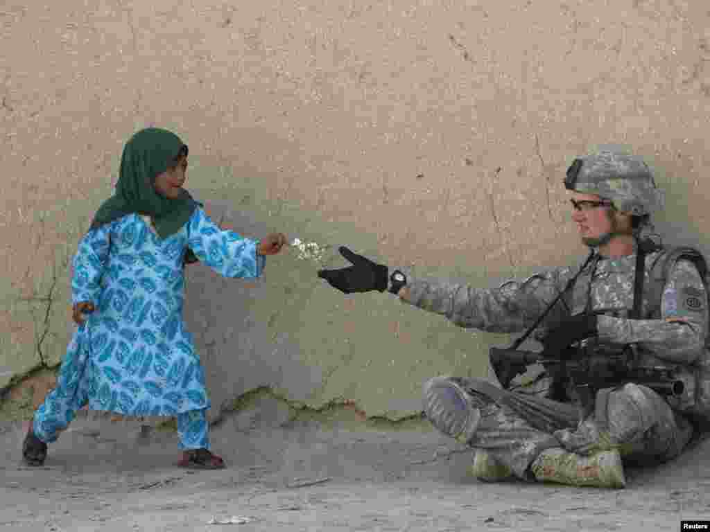 A U.S. Army soldier receives flowers from an Afghan girl during a patrol in the Arghandab valley in Kandahar Province. - Photo by Baz Ratner for Reuters