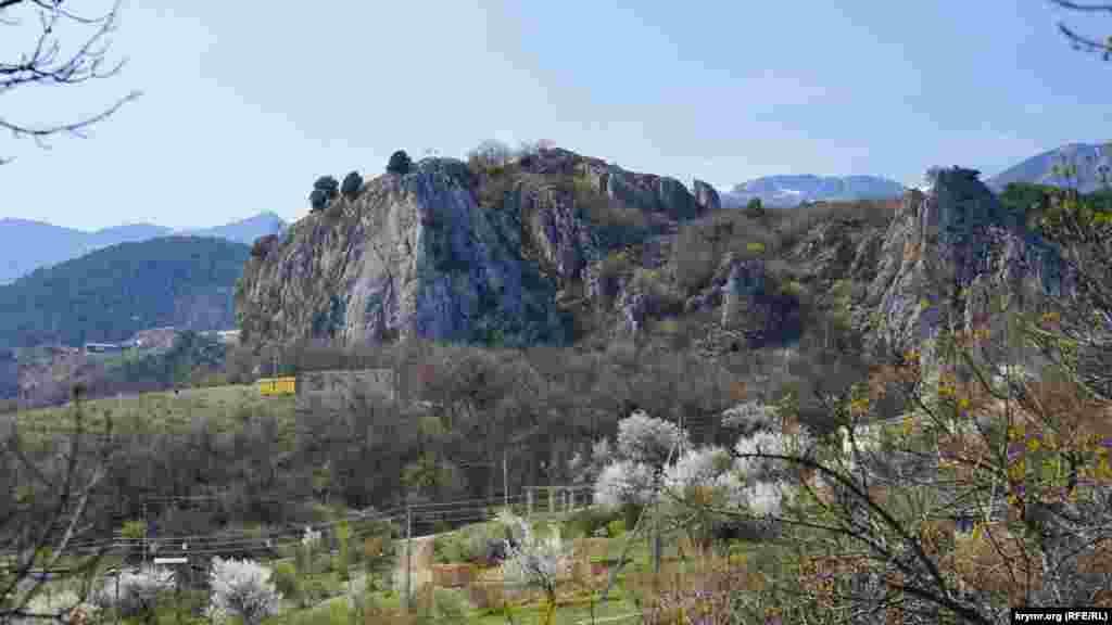 Скала Красный Камень в северо-западной части Гурзуфской долины около Ялты. Свое «цветное» название она получила из-за розовато-желтогомраморовидного известняка