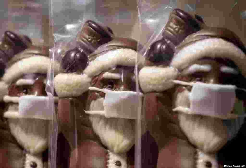 Шоколадні Санта-Клауси в масках для обличчя, виставлені у вітрині кондитерської крамниці в центральній частині Франкфурту. Німеччина, 22 листопада 2020 року