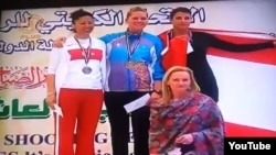 Maria Dmitrenko (top center) atop the podium following her first-place finish at the Grand Prix shooting championships in Kuwait this month.