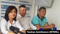 Бекзат Мақсұтханұлы (ортада) адвокат Айман Омаровамен бірге баспасөз мәслихатында отыр.