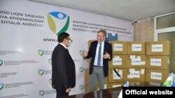 Посол США в Узбекистане Дэниел Розенблюм передает гуманитарную помощь представителю Агентства санитарно-эпидемиологического благополучия.