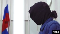Murder suspect Yevgenia Khasis, wearing a black hood over her head, sits in the defendant's cage of a Moscow court.
