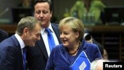 Premieurl Poloniei, Donald Tusk discutînd cu Angela Merkel, cancelarul german, alături de premierul britanic David Cameron la Bruxelles