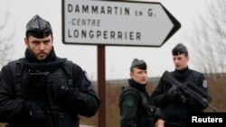 French gendarmes secure the roundabout near the scene of a hostage taking at an industrial zone in Dammartin-en-Goele, northeast of Paris on January 9, 2015