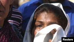 A woman weeps for her missing son at the site of one of the bombings in Lahore.