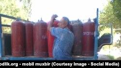 Мужчина берет баллон сжиженного газа. Иллюстративное фото.
