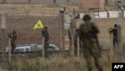 یک عضو « یگان های مدافع خلق» ، در مقابل سربازان ترک، در حال حمل پرچم این گروه در شمال سوریه و مرز با ترکیه است.