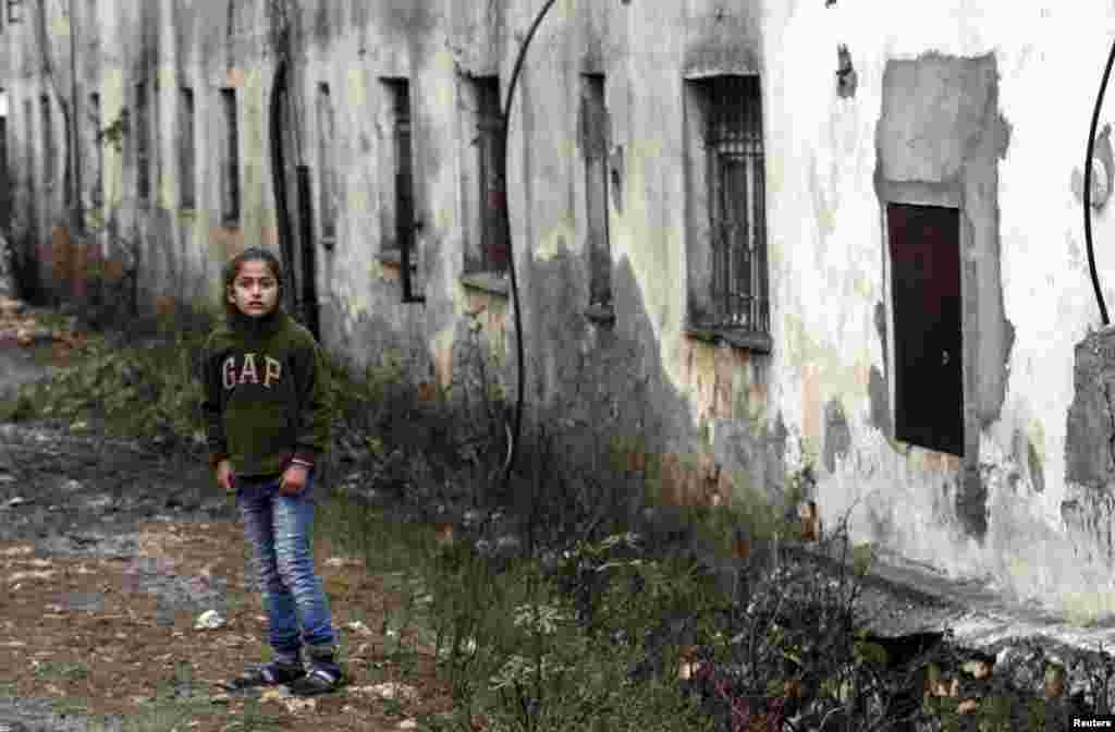 An Albanian girl stands in front of her dilapidated house northwest of the capital Tirana. (Reuters/Arben Celi)