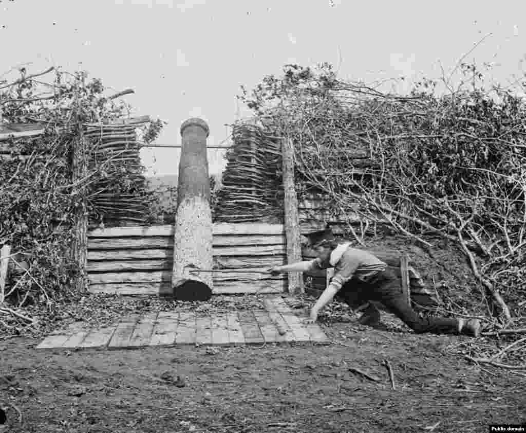 A man pretends to fire a Quaker gun. The dummy weapons were sometimes used to buy a retreating army time as they hauled away their real cannons under cover of darkness. Quaker guns were named after a Christian sect devoted to nonviolence.