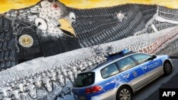 "A German police car passes a mural painting featuring the emblematic U.S. eagle with a badge that reads ""National Security Agency worldwide"" at the Ehrenfeld railway embankment in Cologne on October 24, with revelations fresh of alleged U.S. eavesdropping on Chancellor Angela Merkel."
