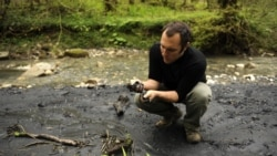 Suren Gazarian examines a black substance that he said was part of a mudslide emanating from an illegal dump, close to the 2014 Olympics construction outside the Black Sea resort of Sochi in April 2011.
