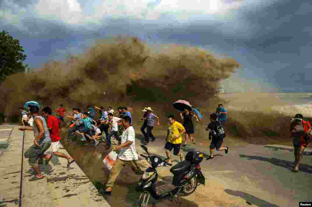 Visitors run away as waves from a tidal bore surge past a barrier on the banks of the Qiantang River in China's Hangzhou Zhejiang Province. (Reuters)