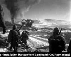 An air strike hits a communist position in December 1950 as U.S. Marines look on.