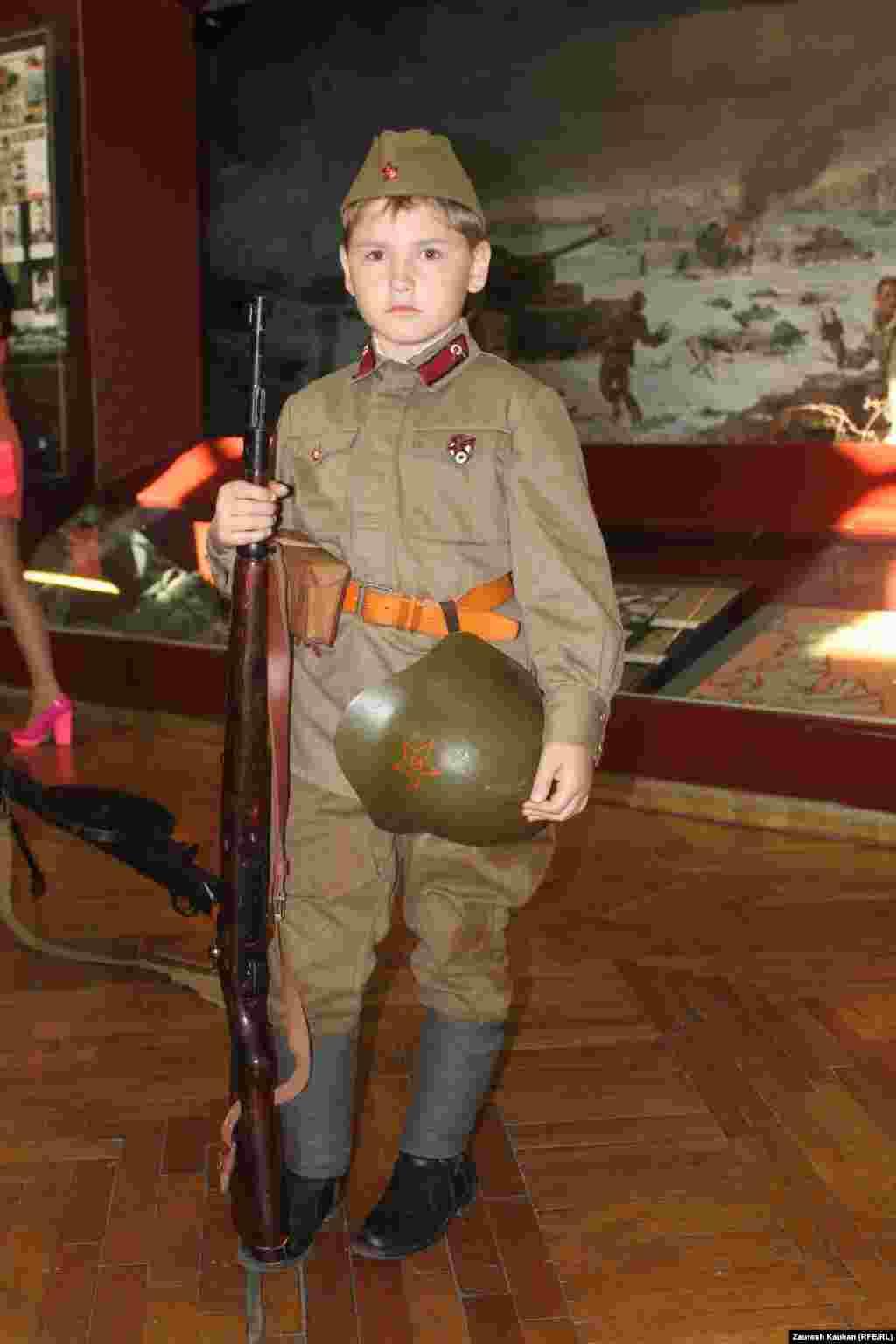 За военной экспозицией был закреплен этот мальчик, одетый в советскую форму времен Второй мировой войны.