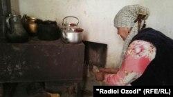 Домохозяйка в Таджикистане растапливает печь. Курган-Тюбе, 17 января 2017 года.