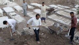 Syria -- Volunteers bury bodies found in some houses after a recent Syrian Air Force air strike in Azaz, some 47 km north of Aleppo, 20Aug2012
