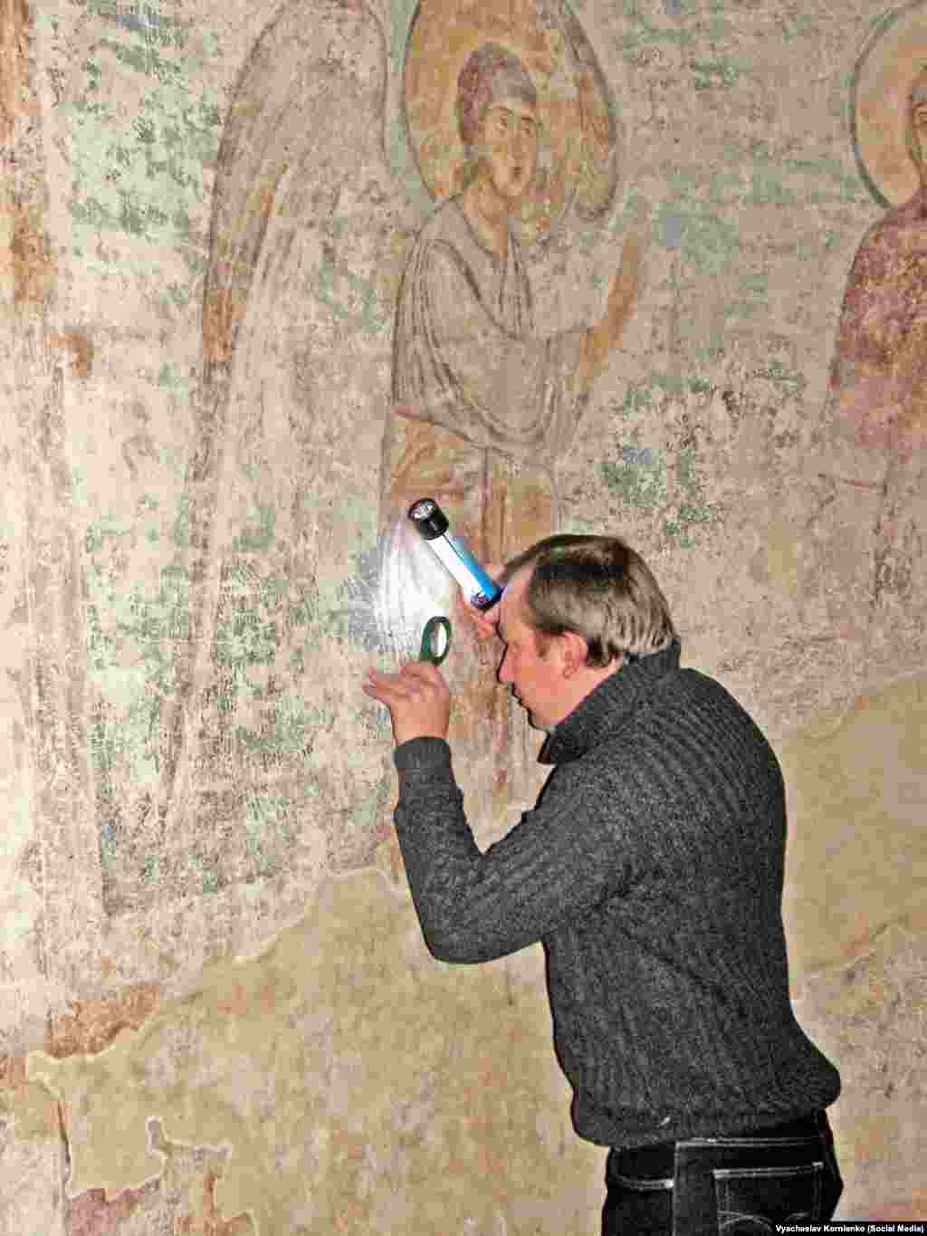 """Kornienko studying old graffiti near the beginning of what would become a 15-year project.  The historian says that """"people wrote graffiti for their contemporaries, but these records allow us to look at the world through the eyes of the people of that time."""""""