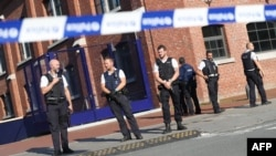 Police stand as they secure the area around a police building in the southern Belgian city of Charleroi following a machete attack on August 6 that left two policewomen wounded.