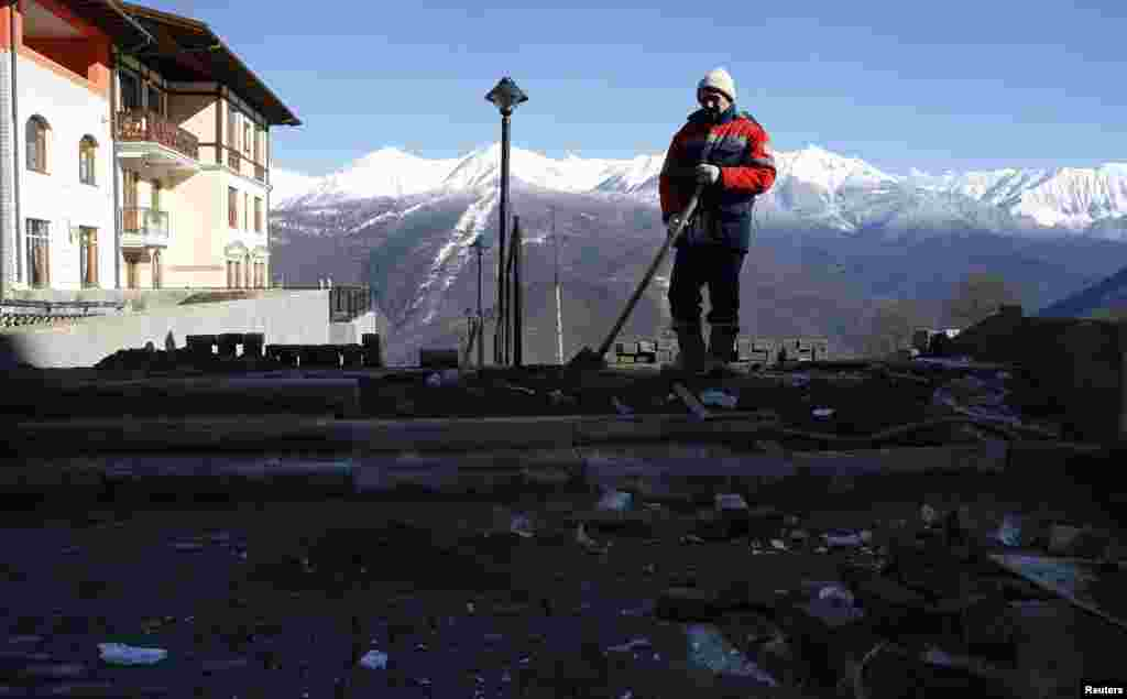 A construction worker clears rubble in one of Sochi's media villages.
